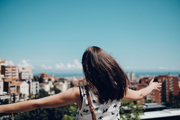 Rear View Of Woman With Arms Outstretched Looking At Cityscape Against Sky