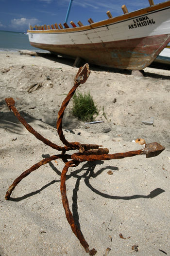 Rusty anchor by moored boat at beach against sky