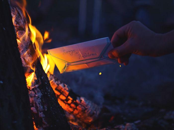 Cropped hand burning envelope at night