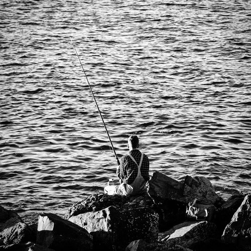 Rear view of fisherman sitting on rock by sea