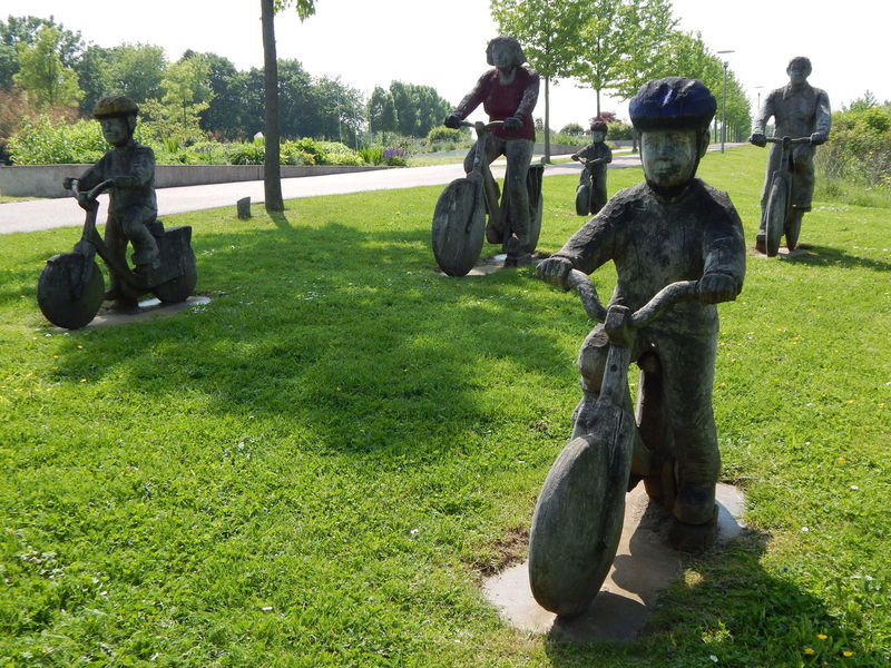 a group of wooden bicyclist in a park in Leverkusen, Germany Art Art And Craft Art, Drawing, Creativity Arts Culture And Entertainment ArtWork Bicycle Bicycles Bicycling Field Grass Grassy Green Color Lawn Monument Monuments Outdoors Park Tranquil Scene Tranquility Wood Wood - Material Wooden Wooden Bicycle Wooden Figure Wooden Figures