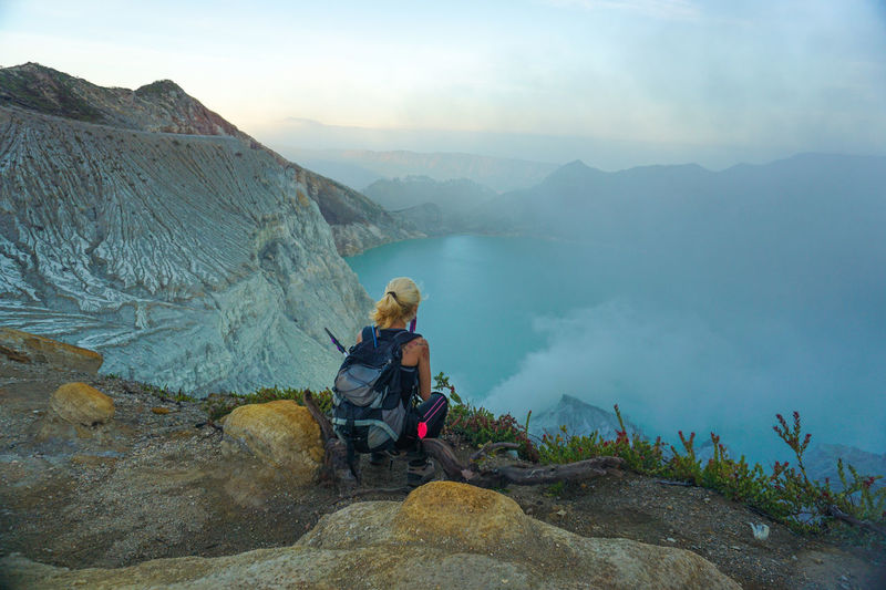 Woman looking at view while sitting on mountain against sky