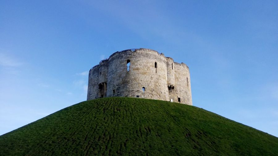 Low angle view of fort on grassy hill against blue sky
