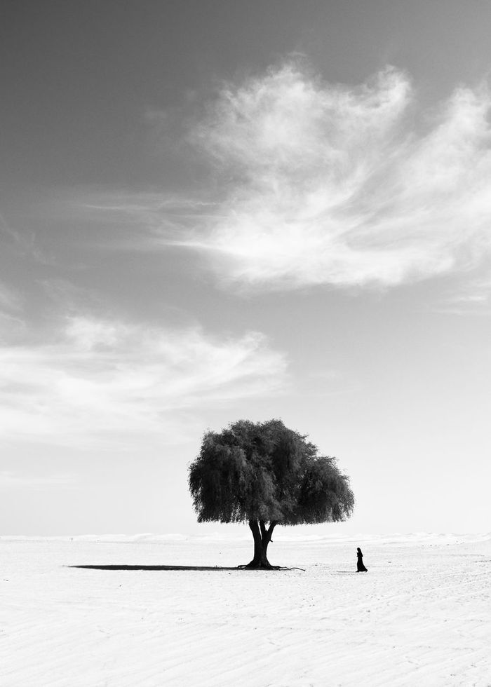 Woman walking on dessert against sky