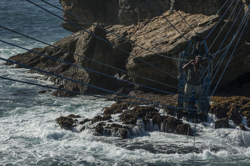 Man on overhead cable car over sea