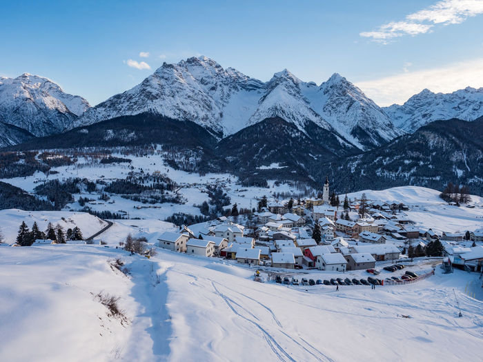 Scenic view of snow covered mountain by alpine village against sky