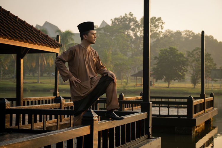 Man Wearing Traditional Clothing While Standing On Built Structure Against Lake During Sunset