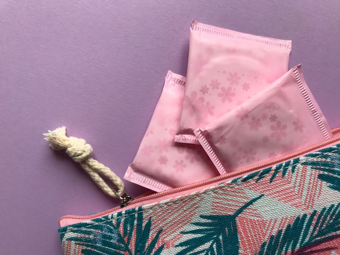 Directly above shot of sanitary pads with purse on purple background