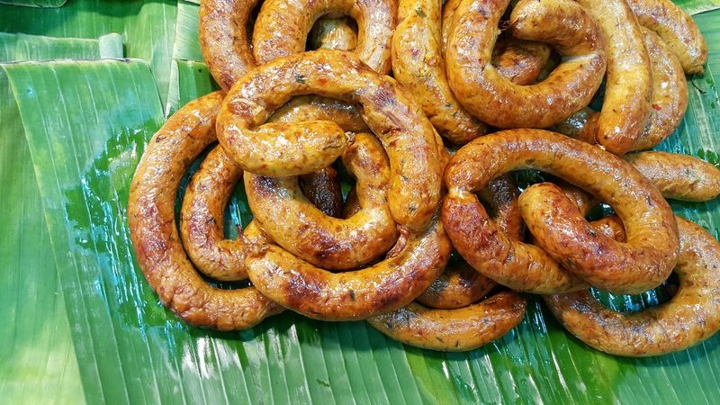 Sai-Uao Spicy Sausage Northern Thailand Style Food Appetizer Grilled Roasted Reccommend Thai Food Guide Tourist Menu Yummy Tasty Smellsgood Delicious Freshness Restaurant Market Local Rural Banana Leaf Texture Packed Oil Eating