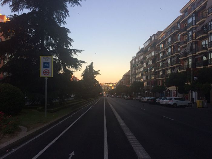 Road by city against sky during sunset
