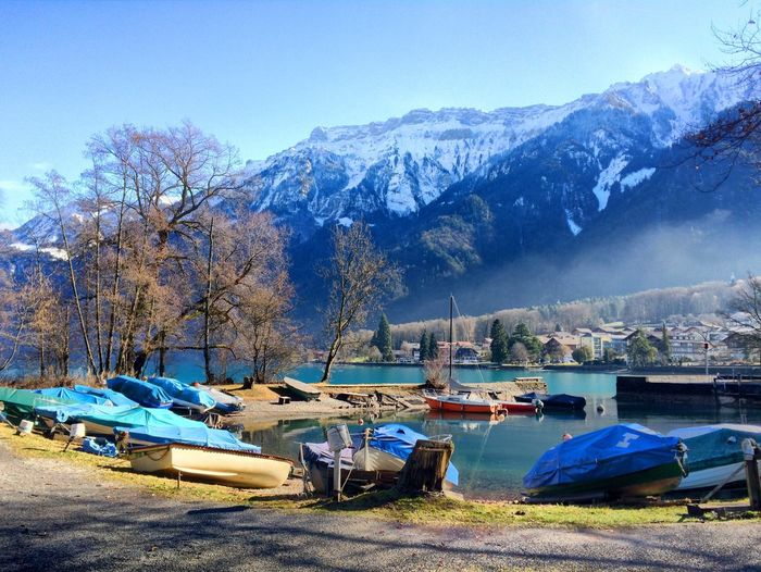 Boats moored by riverside against snowcapped mountains