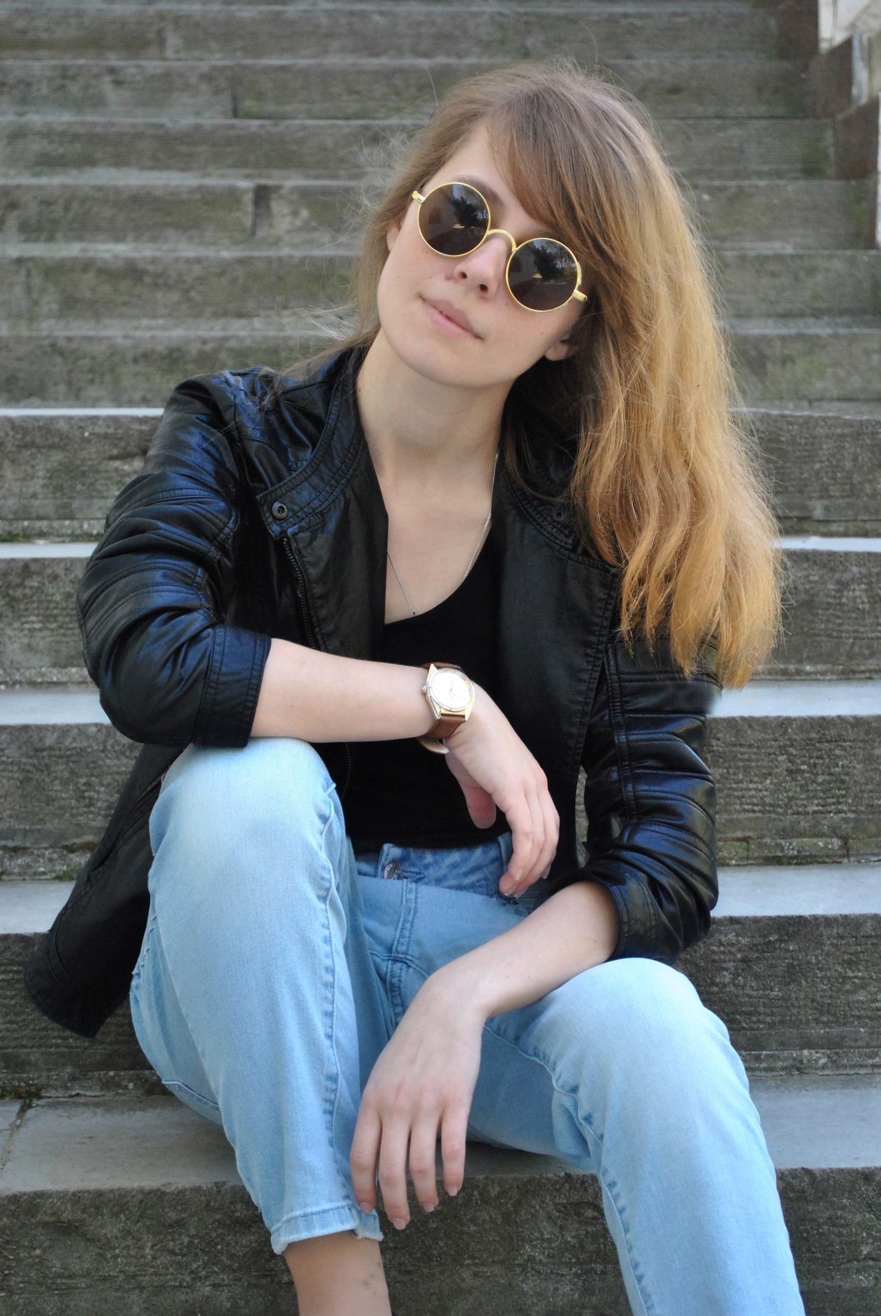 real people, one person, lifestyles, sitting, young adult, casual clothing, leisure activity, front view, staircase, young women, glasses, long hair, day, hair, hairstyle, three quarter length, architecture, fashion, outdoors, jeans, beautiful woman, teenager, contemplation