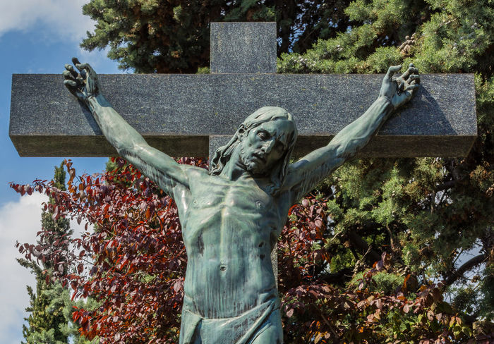 Statue of Jesus Christ crucified against some trees. Jesus Christ on cross. Jesus christ statue in the cemetery. Ancient Bible Blue Calvary Catholic Catholicism Christ Christian Christianity Cross Crucified Crucifix Crucifixion Death Dramatic Easter Europe Face Faith Friday God Holy INRI Jesus Man