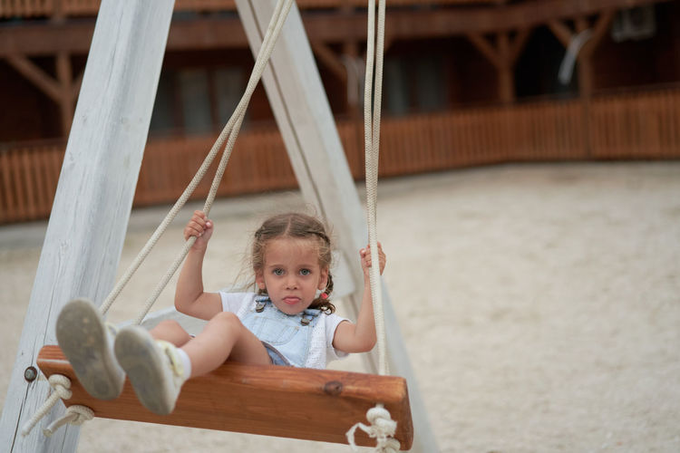 Portrait of cute girl sitting on swing at playground