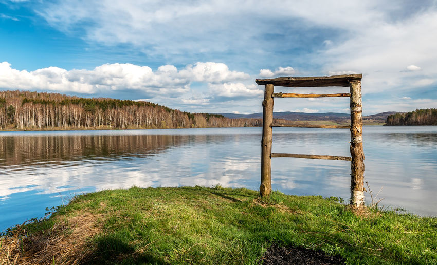 Wooden posts on lake against sky