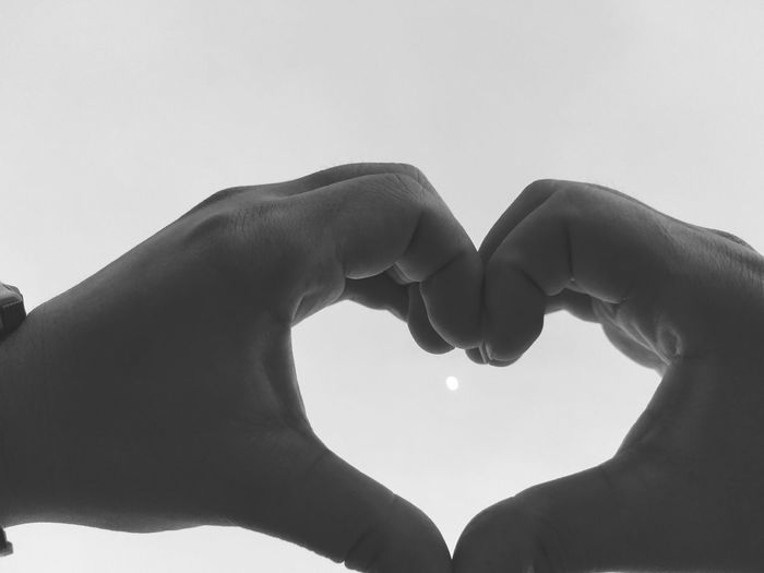 Cropped Hands Making Heart Shape Against Clear Sky