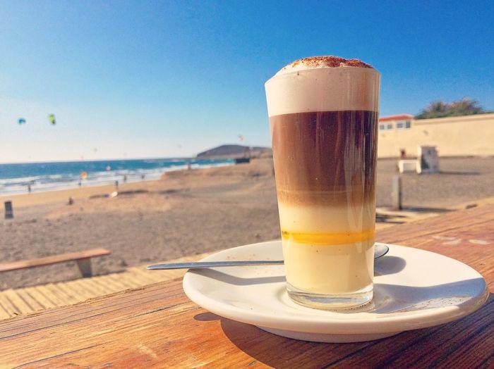 Café en el mar Barraquito Con Licor Barraquito Coffee Cafe Drink Refreshment Food And Drink Glass Water Beach Land Sea Sky Nature Table Sand Sunlight