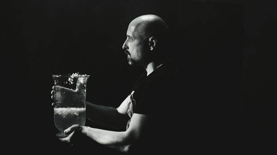 Profile View Of Bald Man Holding Drink In Container Against Black Background