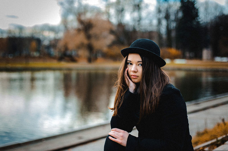 Portrait of young woman wearing hat standing in water