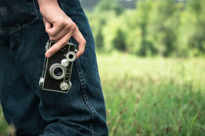 Midsection of man with holding camera while standing on field