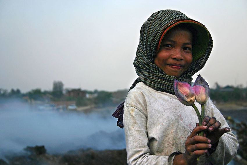 A young girl with flowers found in the waste at the garbage dump in Phnom Penh, Cambodia in 2005. One of my early photos from the beginnings of my photography. Cambodia Phnompenh Phnom Penh Landfill Documentary Poverty Garbage Dump Children Mid Adult Adult Winter People