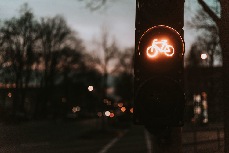 Illuminated bicycle lane sign on stoplight in city at dusk