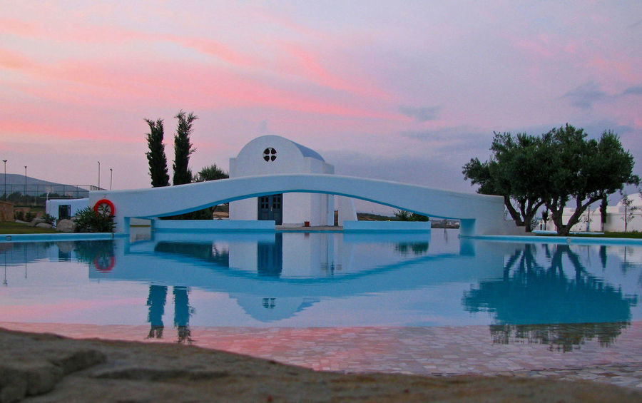 Typical Greek church built within the hotel grounds surrounded by an infinity pool on the edge of the Mediterranean Sea where religious functions and weddings are regularly held Azure Bridge Built Structure Church Double Reflection Infinity Pool Outdoor Photography Outdoors Panorama Panoramic Photography Pink Romantic Sunset Water Reflections