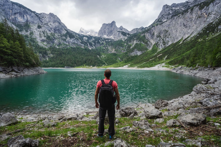 Rear view of man standing on lake against mountains