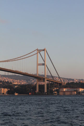 Bosphorus bridge over strait against clear sky during sunset