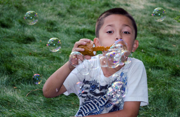 A young boy has fun blowing bubbles Toys Adult Blowing Boys Bubble Bubble Wand Child Childhood Children Only Close-up Day Enjoyment Fragility Freshness Front View Grass Hispanic Leisure Activity Mid-air Nature One Boy Only Outdoors People