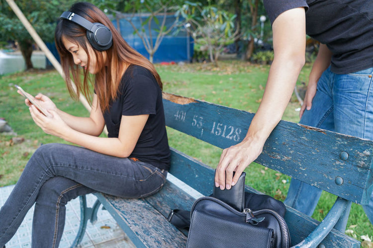 Midsection of man removing wallet from bag while woman using phone on bench