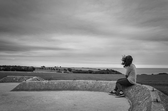 Young woman looking at the sea at the Batteries of Longue-Sur-Mer in Normandy a cloudy day Backgrounds Casual Clothing Cloud Cloud - Sky Day Footpath Horizon Over Water Ledge Life Loneliness Normandy One Person Outdoors Sadness Scenics Seascape Single Tree Sky Solitude Summer Tranquil Scene Tranquility Young Young Adult Young Women