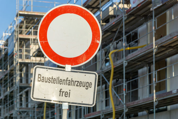 """construction site with sign """"baustellenfahrzeug frei"""" - construction site vehicle free Construction Scaffolding Built Structure Communication Geometric Shape Information Information Sign Low Angle View No People Outdoors Road Road Sign Sign Text Warning Sign"""