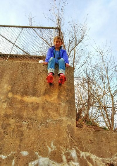 Low angle portrait of girl sitting on retaining wall