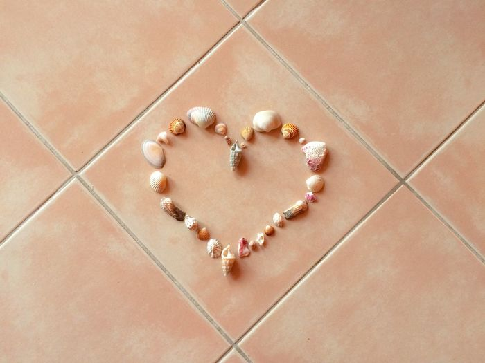 High angle view of heart shape made by seashells on tiled floor