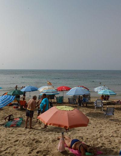 a beach Water Sea Beach Sand Summer Relaxation Incidental People Canopy Sky Horizon Over Water Beach Umbrella Parasol Shore Shelter Umbrella Sun Lounger Sandy Beach Sunshade