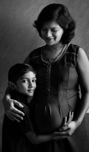 Portrait of a smiling boy standing next to mother