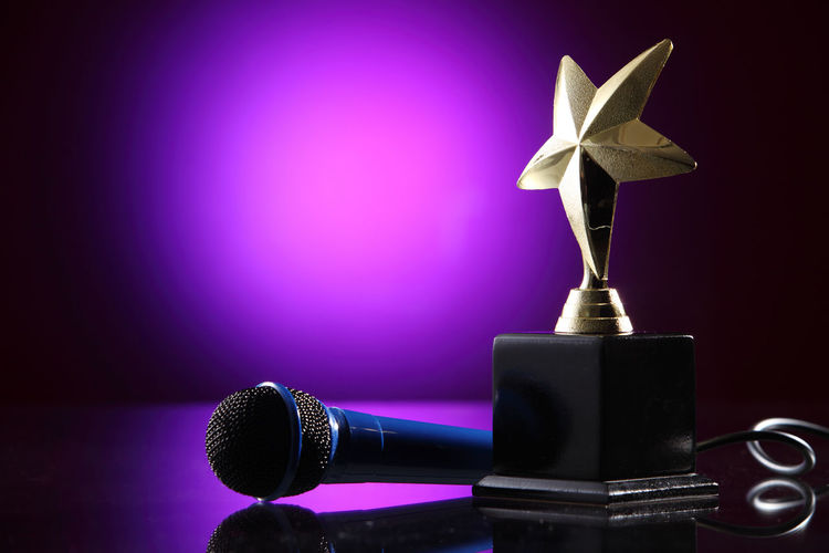 microphone and golden trophy on the purple background AWARD Celebration Champion Contest Effort First Place  Golden Shiny Singing Contest Trophy Ceremony Competition Cup Glow Honor Leadership Light Spot Metallic Microphone Performance Prize Purple Success Victory Winner