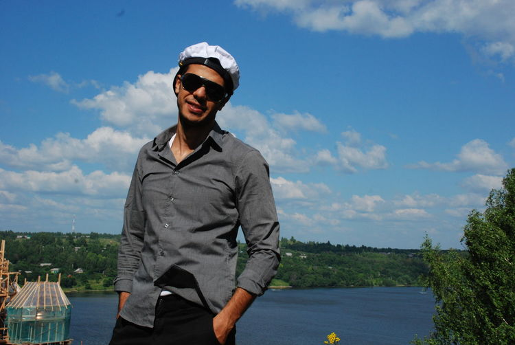 Young man wearing sunglasses standing against volga river