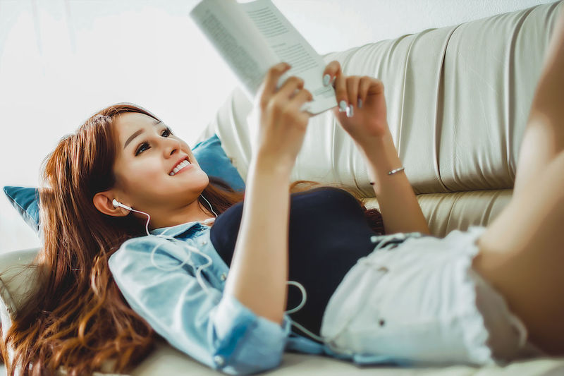 The use of free time by reading books, listening to music Educational ideas from books Young Women Young Adult Lying Down Real People Lifestyles Portrait Relaxation Beautiful Woman Free Time Reading Ready For Summer Listening To Music Books