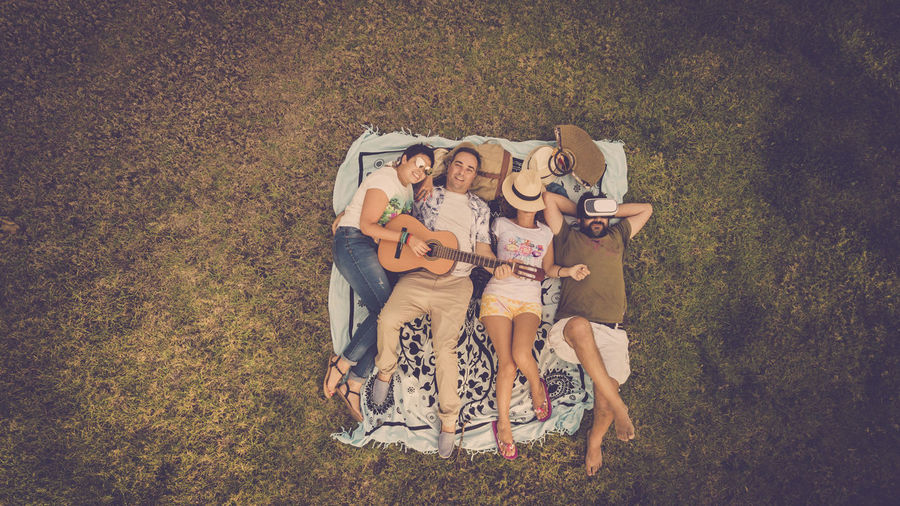 High angle view of friends lying down on field