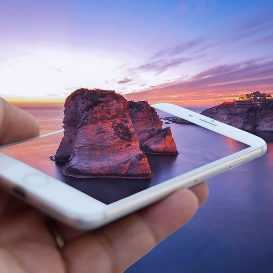 Digital composite image of person holding mobile phone with mountain against sky during sunset