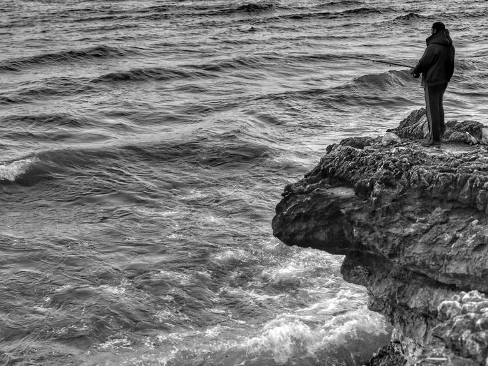 Rear view of man standing on rock in sea