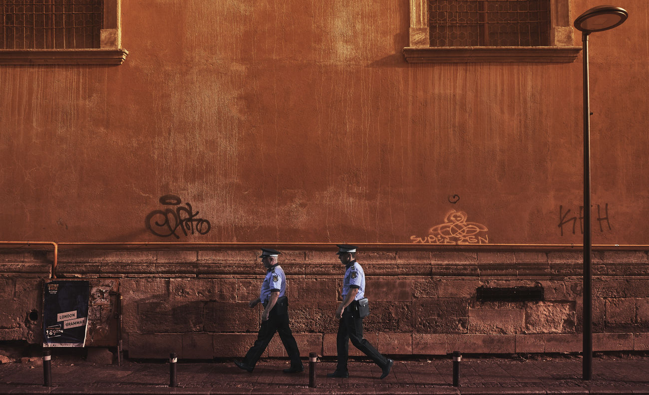 REAR VIEW OF TWO PEOPLE WALKING ON WALL