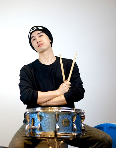 Asian  Band Males  Artist Arts Culture And Entertainment Bands Casual Clothing Chinese Drum Drum - Percussion Instrument Drummer Drumstick Front View Holding Indoors  Leisure Activity Lifestyles Music Musical Equipment Musical Instrument Musician One Person Real People Studio Shot Young Adult