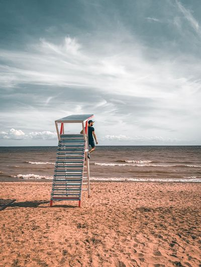 Man standing on lookout tower at beach