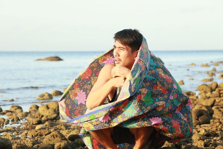 Man wrapped in blanket crouching on rocky shore
