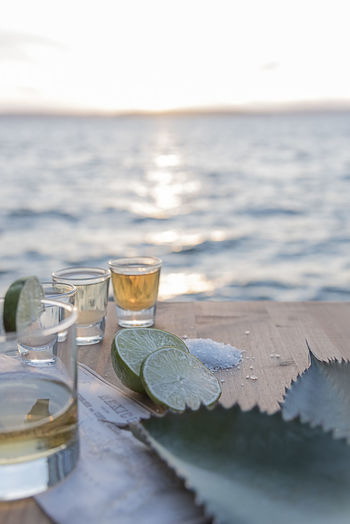 Close-up of tequila shots by lemon and salt on table by beach against sky