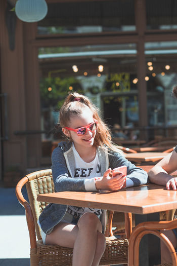 Teenage girl using smart phone while sitting with friend at table in cafe