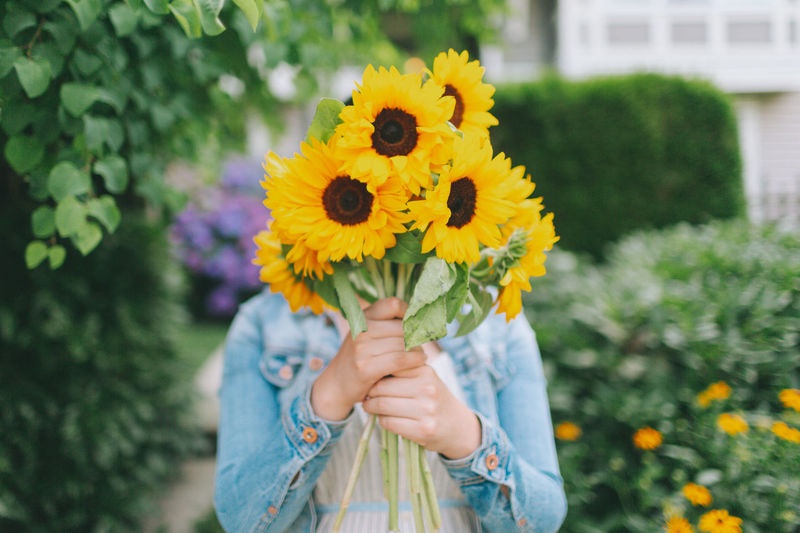 A woman holding a bouquet of sunflowers. Obscured Face Sunflower Outdoors Woman Holding Bouquet Sunflowers